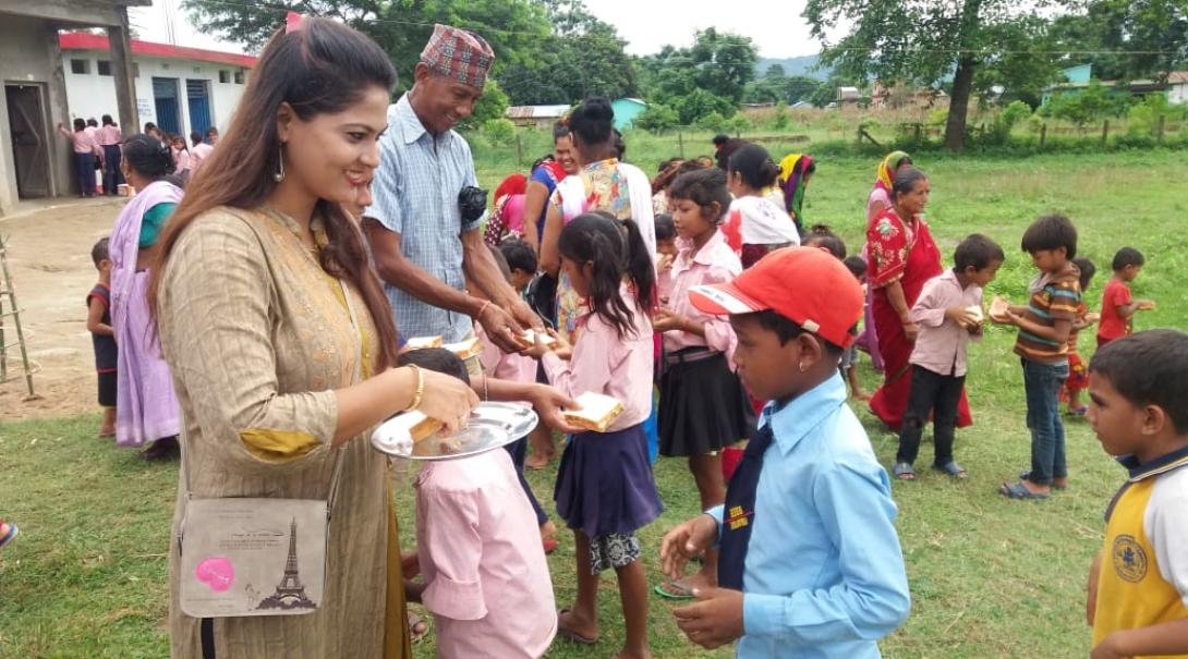 Local staff and volunteers hand out meals to the students for lunch in Nepal